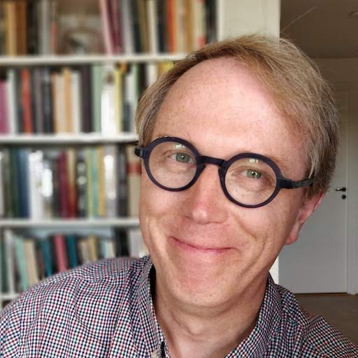 Headshot of Peter Rukavina, a white man with blond hair, wearing a checked button-down shirt and blue eyeglasses, against a blurred background of a bookcase.